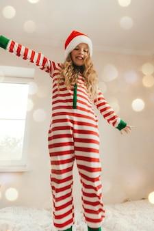 잠옷을 입은 귀여운 행복한 어린 소녀가 집, 어린 시절 개념, 크리스마스에서 흰색 침대에서 뛰어올랐습니다.