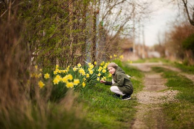 Милая счастливая маленькая девочка в стране весной пахнущие желтые нарциссы