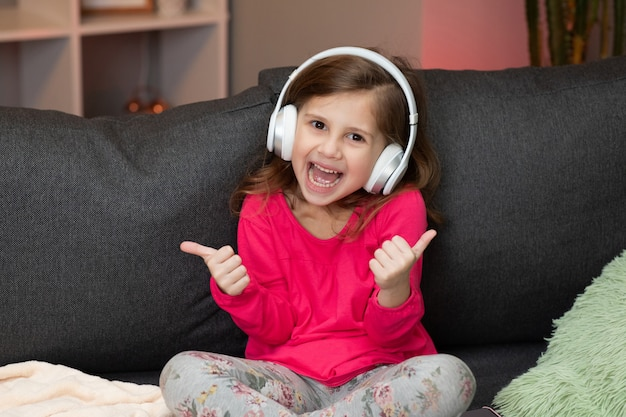 Cute happy little girl listens to music on wireless headphones. funny little girl dancing, singing and moving to rhythm. kid wearing headphones.
