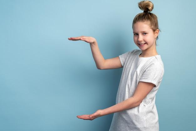 青い壁のコピースペースにコンセプトを示すかわいい、幸せな、小さな女の子