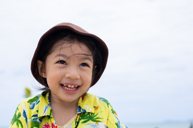 A cute happy little girl smiling at beach.