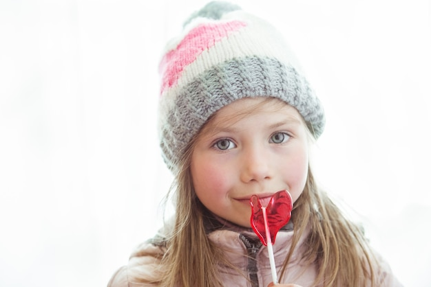 Cute happy little girl with lollipop candy with copyspace