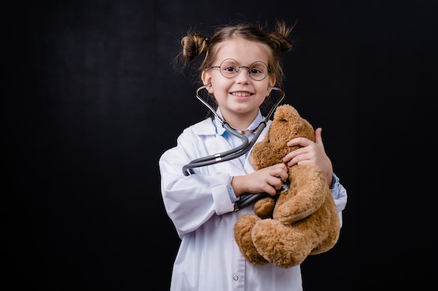 Cute happy little girl with stethoscope examining teddybear in front of camera against black space