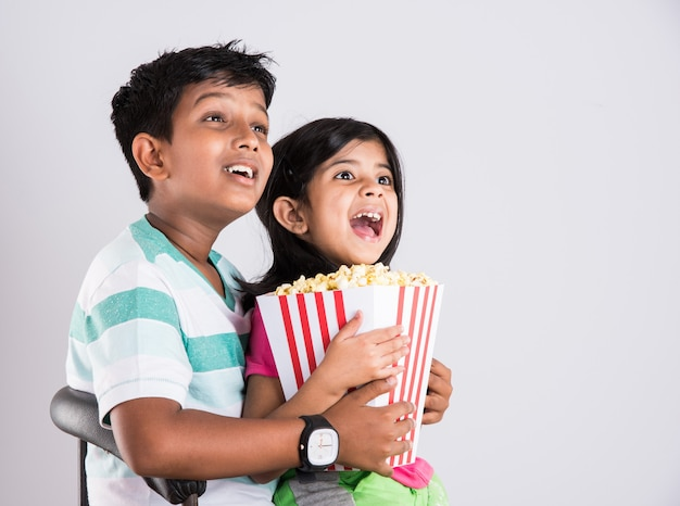 Cute happy little indian boy and girl or siblings eating popcorn and watching television while sitting on chair