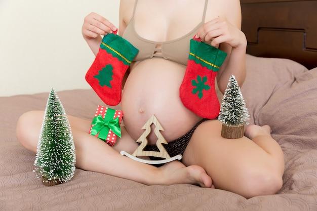 집에서 크리스마스 장식으로 잠옷을 입은 귀여운 행복한 임산부. 큰 배를 가진 어머니, 배 위에 손. 메리 크리스마스 휴일입니다. 새 해 이브 개념입니다.