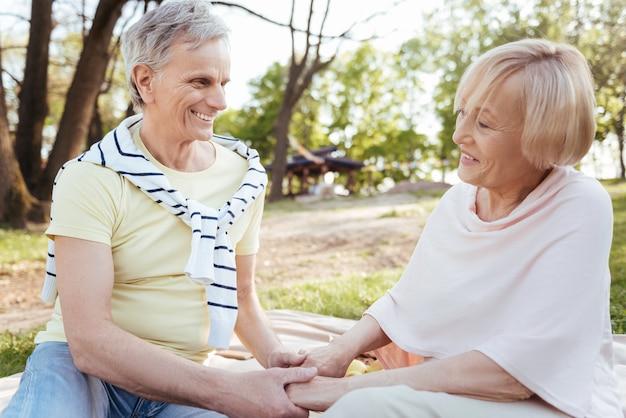 手をつないで、屋外でピクニックを楽しみながらケアを表現するかわいい幸せな引退したカップル