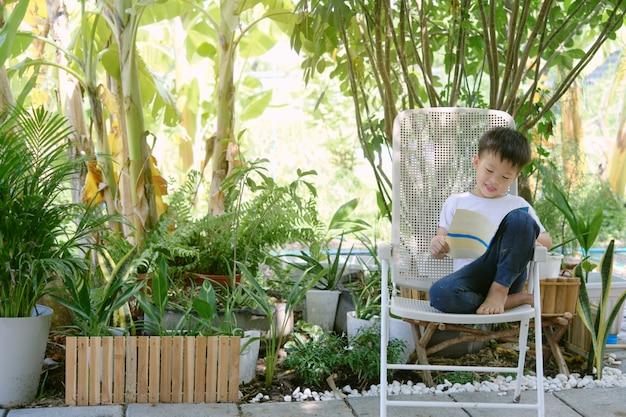 자연의 집 정원에 앉아 휴식을 취하는 동안 책을 읽고 있는 귀여운 행복한 미소 짓는 아시아 소년