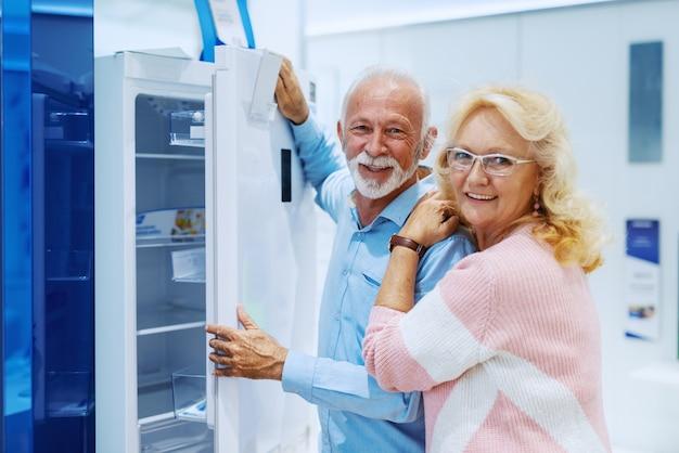 自宅に新しい冷蔵庫を選ぶかわいい幸せな笑みを浮かべて白人シニア。テックストアのインテリア。