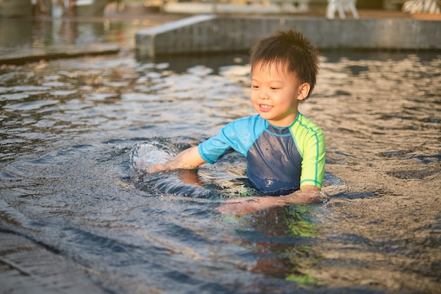 Cute happy smiling little asian 5 years old boy child in swimming suit enjoy playing at swimming pool in sunny summer day, happy kid having fun on summer vacation at the hotel at sunset
