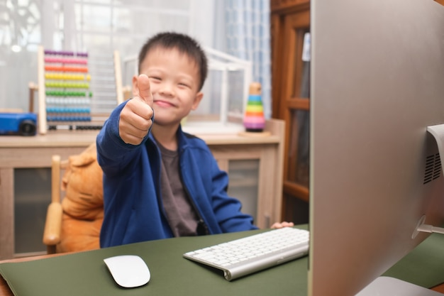 Cute happy smiling little asian kid showing thumbs up while using personal computer at home, kindergarten boy studying online, attending school via e-learning