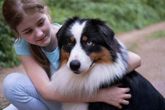 Симпатичная счастливая девочка-подросток обнимает трехцветную собаку австралийской овчарки летом