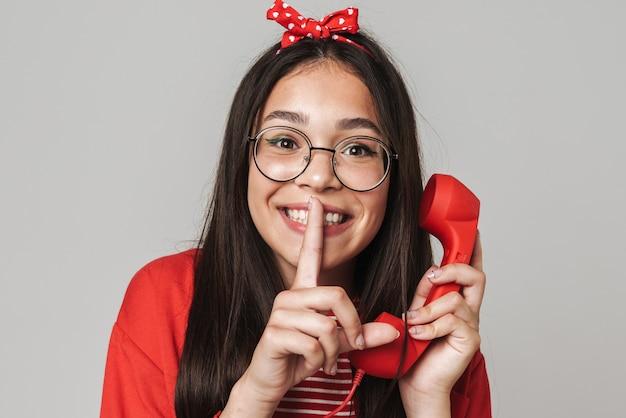 Милая счастливая девочка-подросток в повседневной одежде стоит изолированно над серой стеной и звонит на стационарный телефон