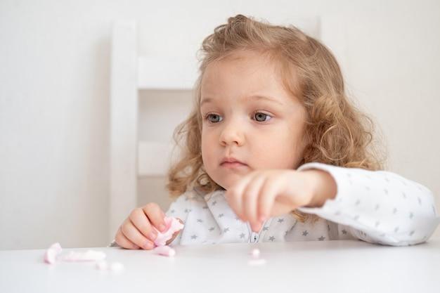 Cute happy toddler girl sculpt figure from plasticine. children creativity. happy family. early development