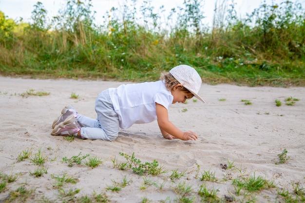 晴れた夏の日に、帽子をかぶったかわいい幸せな幼児が砂の中の田舎道に沿って四つん這いで這う。