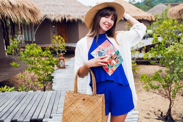 笑顔で見ているノートブックとかわいい幸せな旅行女。青いジャンプスーツ、麦わら帽子とバッグ、サングラス。ブルネットの少女は彼女の素晴らしい豪華なヴィラでポーズします。