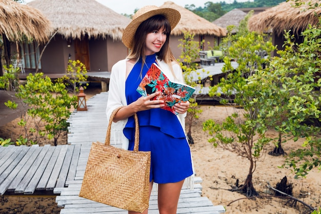 Cute happy traveling woman with notebook smiling a.blue jumpsuit , straw hat and bag, sunglasses. brunette girl posing  in her amazing luxury villa.