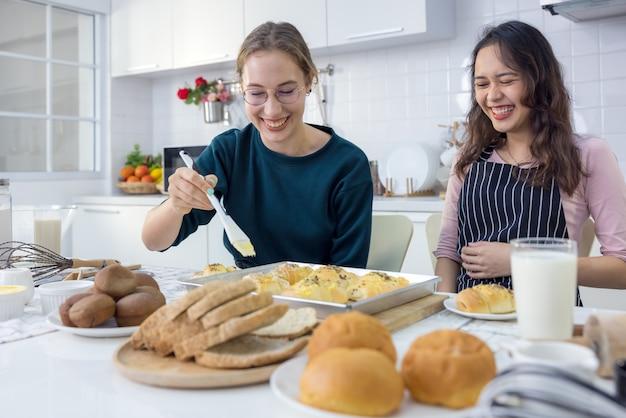 Милые счастливые двое, красивая пекарня, выпекающая сладости. женщины хорошо провели время на уроке выпечки хлеба и вместе руками склеивают тесто на кухне, чтобы вместе испечь пироги.