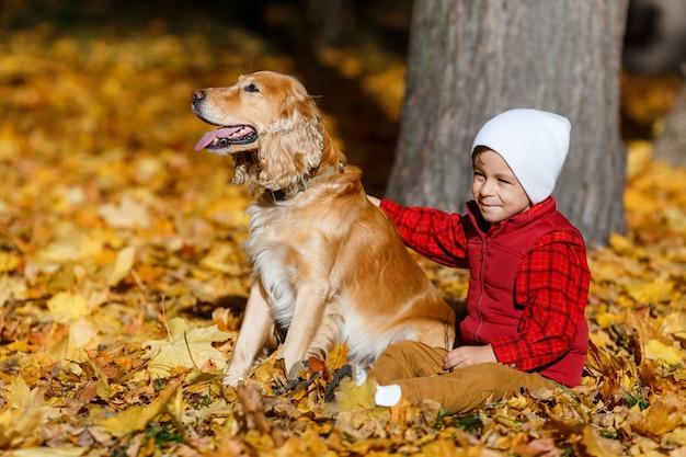 웃 고 노란 잎 사이에서 강아지와 함께 연주 빨간 셔츠에 귀여운, 행복, 백인 소년. 가을 공원에서 재미 작은 아이. 아이들과 애완 동물, 행복한 가족 사이의 우정의 개념
