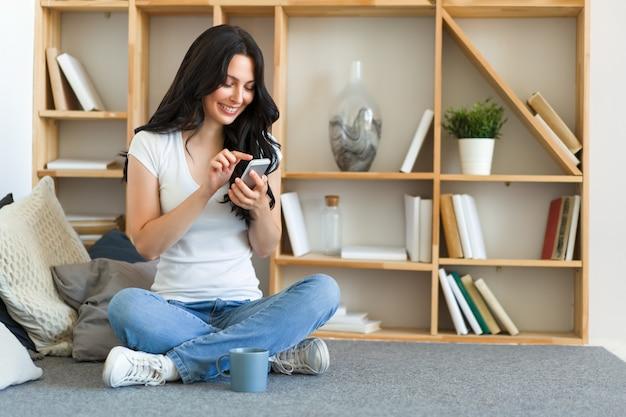 携帯電話を持って、チャットやロマンチックなメッセージを送信するためにモバイルデートアプリケーションを使用してかわいい幸せな女性