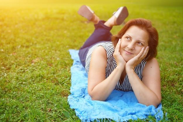 休んでいる緑の草の上に横たわるかわいい幸せな女