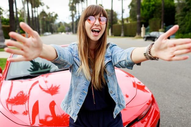 Donna felice sveglia in vetri rosa che fa autoritratto vicino a un'auto sportiva convertibile rossa incredibile in california.