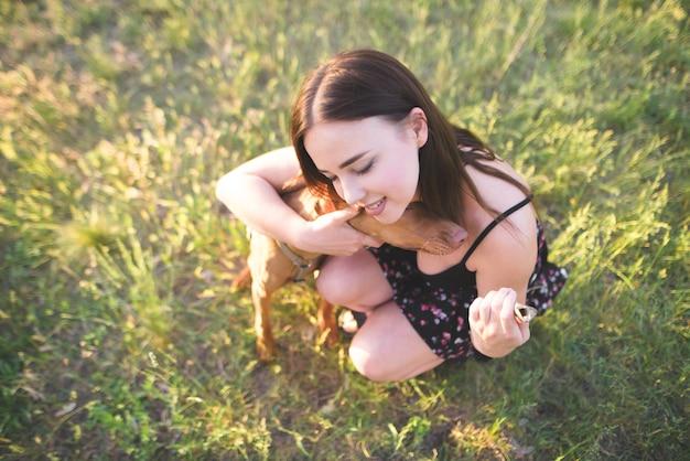 公園の芝生の上に座っていると犬を抱き締めるかわいい幸せな女。幸せな女は犬を抱擁し、笑顔します。