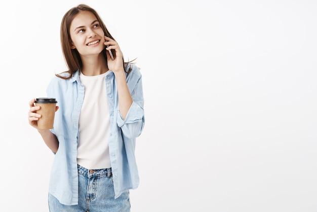 Милая счастливая женщина выпивает в кафе возле офиса, держа смартфон возле уха, мечтательно глядя в правом верхнем углу, беззаботно улыбаясь, стоя с бумажным стаканчиком кофе в руке