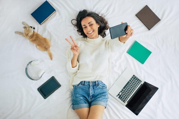 かわいい幸せな若い美しい女性は、彼女の小さな犬と勉強のためのいくつかのものと一緒に自宅のベッドに横たわっています。ノートパソコンと携帯電話を持つ女の子