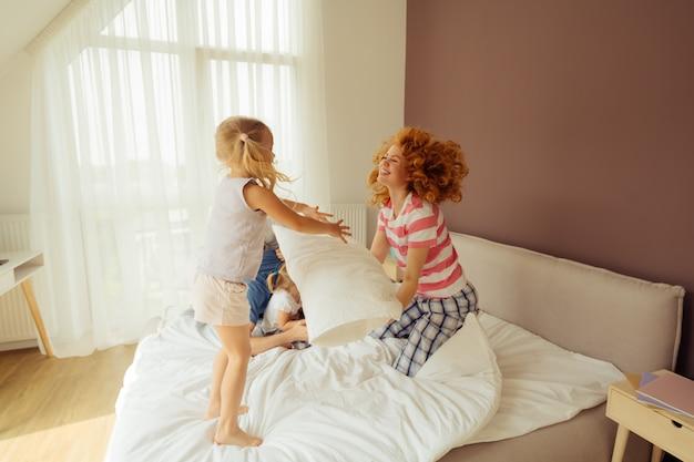 Милая счастливая молодая девушка прыгает на кровати