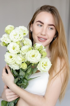 Cute happy young girl in white blank t-shirt, holding a bouquet and looks at the of flowers, enjoying the smell. beautiful blond teen girl with braces on her teeth smiling