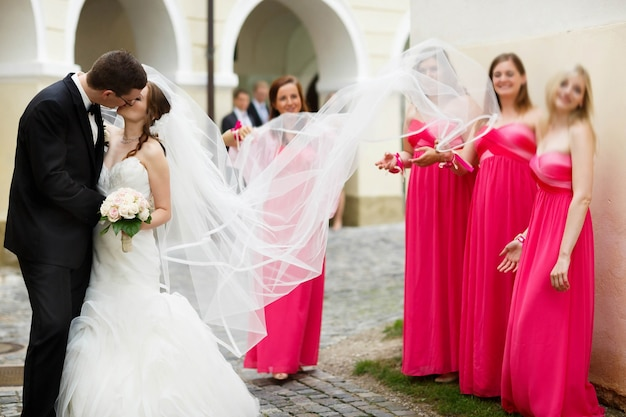 Cute giovane sposo felice e sposa baciano sullo sfondo whitnesses nei vestiti rosa