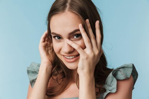 カメラを探しているかわいい幸せな若い女性。