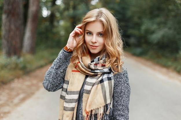 체크 무늬 빈티지 스카프에 세련된 봄 코트에 귀여운 행복 한 젊은 여자는 따뜻한 봄 날에 공원에서 산책