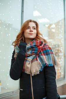 모직 스카프가 달린 검은 장갑에 세련된 겨울 코트에 귀여운 행복 한 젊은 여자가 화환으로 장식 된 상점 창을 배경으로 서 있습니다. 도시에서 걷는 명랑 소녀