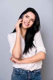 Милая счастливая молодая женщина с густыми черными волосами разговаривает по телефону со своим парнем с зубастой улыбкой, стоя на сером пространстве