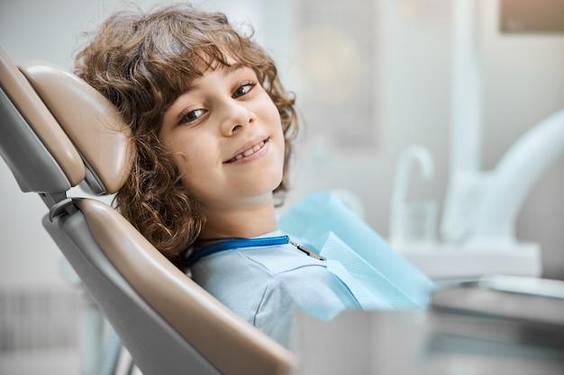 치과 검진을 할 준비가 된 치과 의자에 앉아있는 동안 웃고있는 귀여운 개암 눈 아이