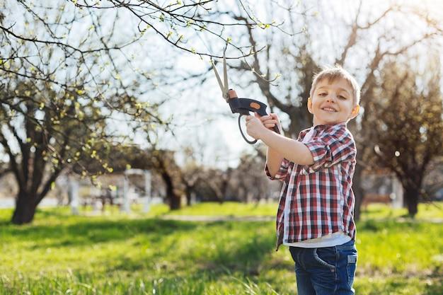 자부심 표정으로 나뭇 가지를 자르고 앞에서 웃는 붉은 격자 무늬 셔츠를 입고 귀여운 개암 눈 아이