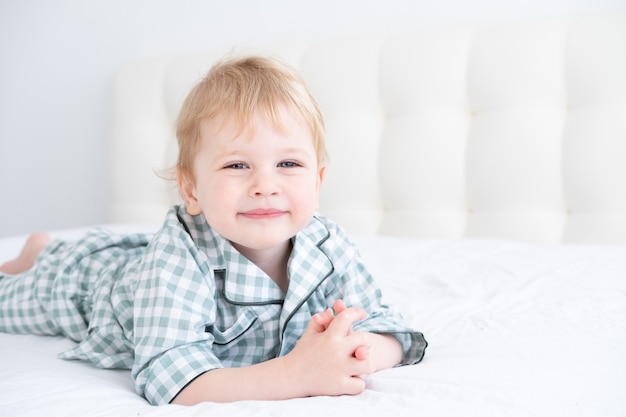 체크 무늬 파자마 집에서 흰색 침대에 누워 재미 귀여운 건강한 유아 금발 소년.
