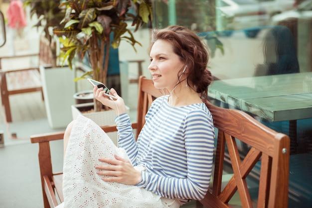 스마트 폰 및 헤드폰 공원 벤치에 앉아 음악을 듣고 귀여운 hipster 백인 십 대 소녀. 현대 젊은이 라이프 스타일