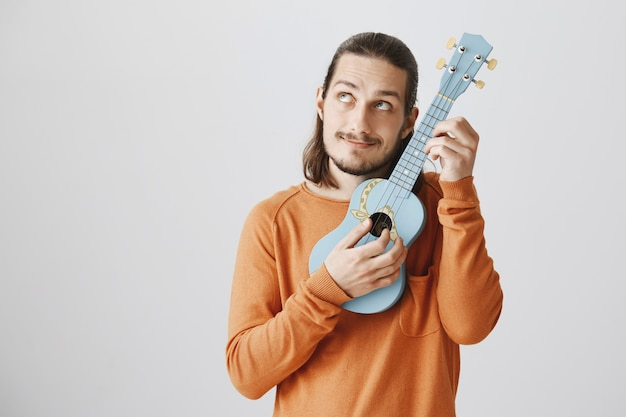Симпатичный хипстерский парень настраивает струны, играя на укулеле