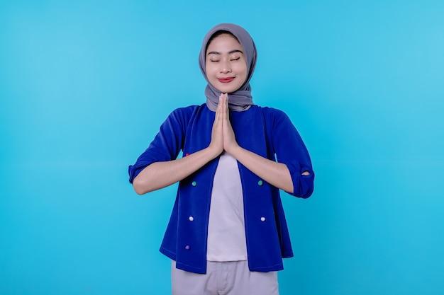 희망에 찬 귀여운 아시아 소녀가 손을 잡고 파란 배경에 대한 조언을 구하는 호의를 구하는 동정을 위해 미소를 지으며 기도합니다