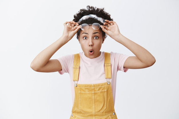 Cute impressed woman taking off glasses from surprise and amazement. charming dark-skinned female model in trendy yellow overalls and headband over hair, saying wow with folded lips, staring
