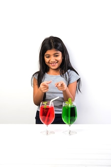 Cute indian asian little girl posing with cold drink or fresh juice at table over white background