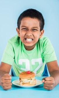 Милый индийский мальчик ест гамбургер, маленький азиатский мальчик и гамбургер, на синем фоне