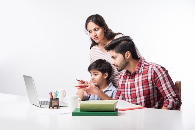 Cute indian boy with father and mother studying or doing homework at home using laptop and books - online schooling concept