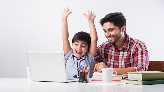 Милый индийский мальчик с отцом или наставником-мужчиной делает домашнее задание дома, используя ноутбук и книги - концепция онлайн-обучения
