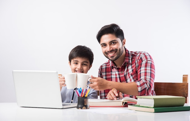 ノートパソコンと本を使用して自宅で宿題をしている父または男性の家庭教師とかわいいインドの少年-オンライン教育の概念