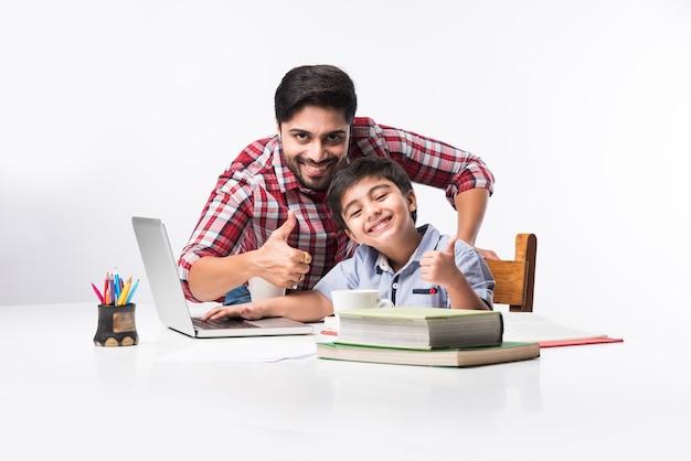 노트북과 책을 사용하여 집에서 숙제를하는 아버지 또는 남성 교사와 귀여운 인도 소년-온라인 교육 개념