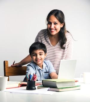 ノートパソコンと本を使用して自宅で宿題をしている母親とかわいいインドの少年-オンライン教育の概念
