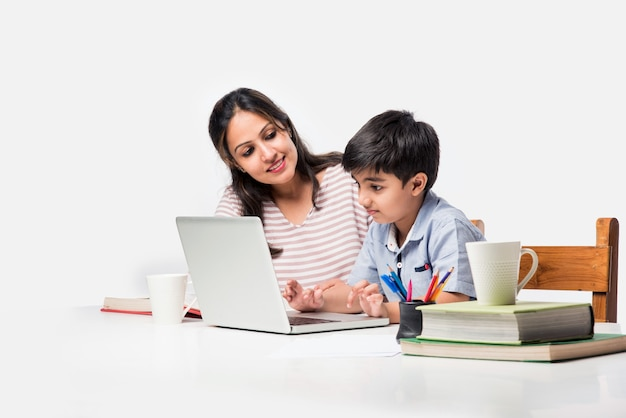 Cute indian boy with mother doing homework at home using laptop and books - online schooling concept